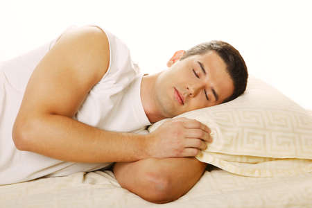 soporific: Handsome young man happily sleeping in bed, isolated.