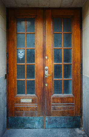 ghost face: Aging door with ghost face over window. Stockholm, Sweden. Stock Photo