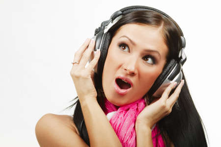 wondering: Young beautiful woman with headphones enjoying the music over white background with open mouth Stock Photo