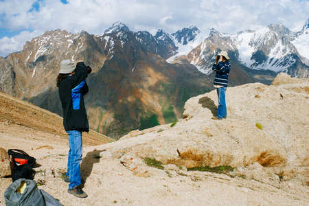 Young tourists with backpacks taking photo of each other from top of a mountain photo