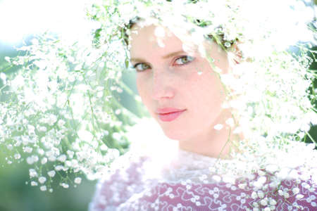 the backlighting: Beautiful young woman on the meadow with white flowers on a warm summer day and backlighting.