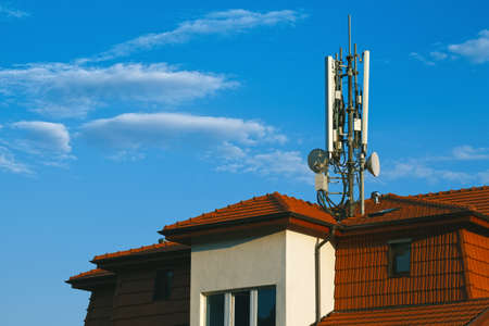 wireless network: Living building with GSM antennas on roof isolated on blue sky Stock Photo