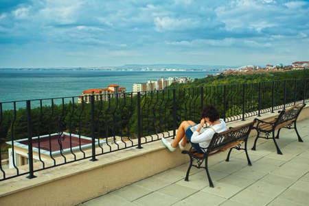 persona sentada: Retrato de la mujer hermosa en la terraza del hotel de prestigio. Vista marítima Foto de archivo