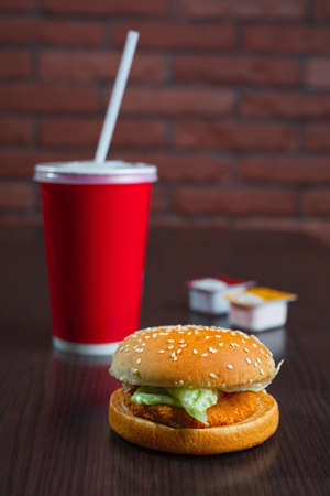 burger and paper cup coke or juice on the wooden table with brick wall on background, vertical orientation Stock Photo