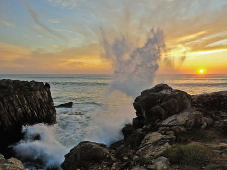 naturaleza: A big wave splashing on the rocks of Peniche, Portugal, with the sunset as background Stock Photo
