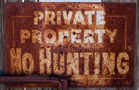An old, rusty  No Hunting  sign