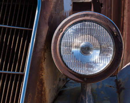 さびた古い車に対して、明るいヘッドライト