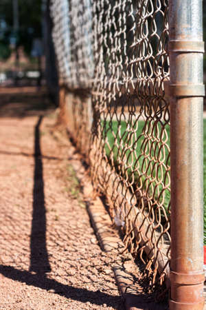 backstop: A dirty fence serves as the backstop behind a baseball diamond in  local park