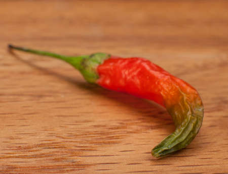 A fresh-picked Cayenne Pepper on an oak table