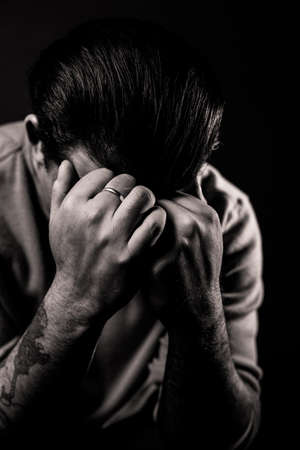 introspective: A man hides his face in angst against a black background Stock Photo