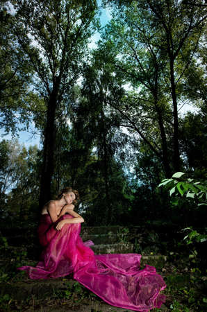 Sensual girl blonde sitting on stairs in the forest photo