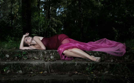 Dramatic scenery - sleeping pretty nymph in red dress photo