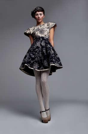 Supermodel fashionable brunette standing in grey  dress Imagens