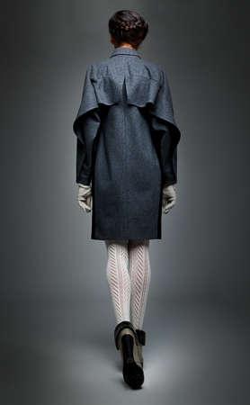 rear end: Slender brunette fashion model in  grey  coat  back elevation drawing Stock Photo