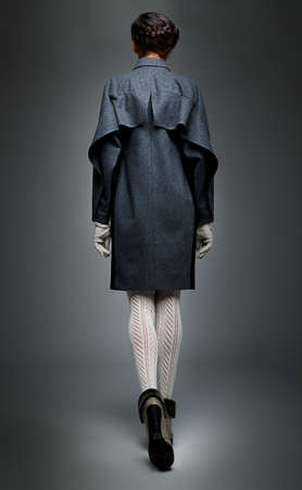 walking away: Slender brunette fashion model in  grey  coat  back elevation drawing Stock Photo