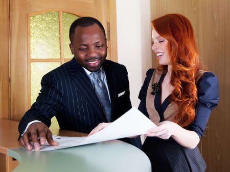 redhead:  Two business people laughing in office space with papers Stock Photo