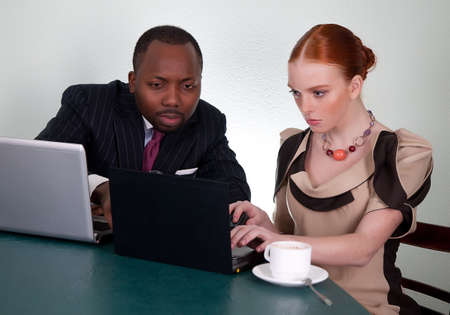 Business colleagues at office desk with two laptops photo