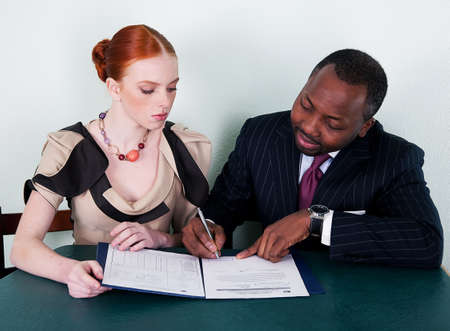 documentation:  Black american man and redhead young woman sitting with documentation Stock Photo