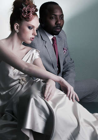 red head:  Two fashion models sitting - black man and red head woman