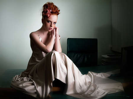 red haired girl: Red haired freckled girl in ivory long dress on office desk sitting - series of photos