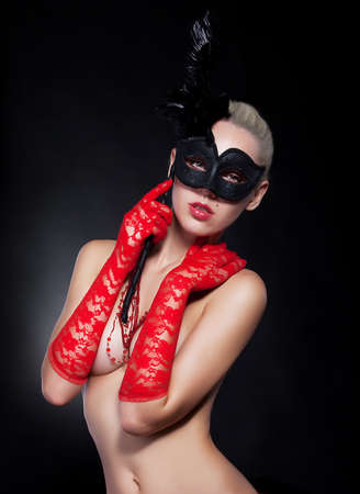 Alluring young blonde girl in black carnival mask studio shot