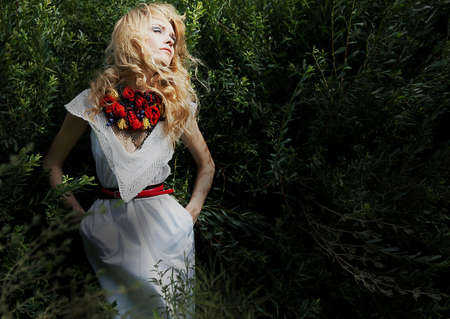 seraphic: Pretty gentle blonde woman over green bushes