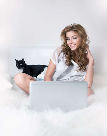 Smiling young girl in white bed with black cat and laptop photo