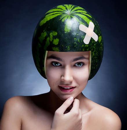 Muchacha encantadora joven con la sandía como el casco en la cabeza sonriendo - serie de fotos