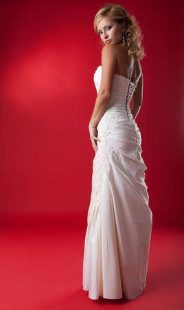 dishy: Elegant fashion model blonde in white wedding dress on red podium  Stock Photo