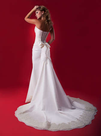 Blonde bride in long wedding dress posing on podium - series of photos  photo