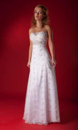 Fashion model blond girl in wedding dress standing on podium photo