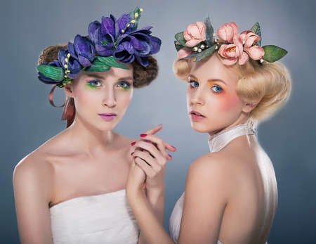 Two lovers nymphs - blonde and brunette in colorful wreath of flowers photo