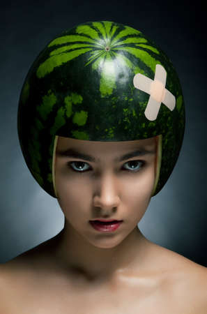 Young hair fashion model with ripe fresh watermelon as a helmet