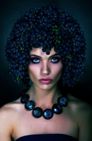 Beautiful fashion model brunette in crown of grapes