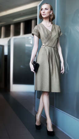 Attractive slender business woman fashion model walking in office interior photo