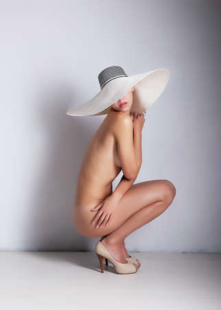 hat nude: Seated nude slender girl in white hat