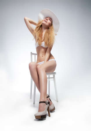 Beautiful bare young blond girl in white lingerie sitting photo