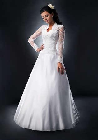 Pretty brede in wedding dress on podium posing photo
