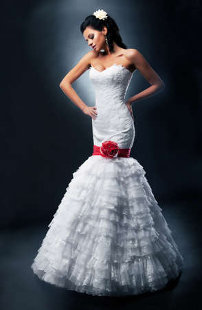 Beautiful bride brunette fashion model in bridal white dress with red ribbon and bow photo