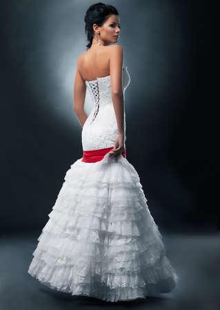 Spectacular fashion model brunette in wedding dress posing on podium Stock Photo - 11927899