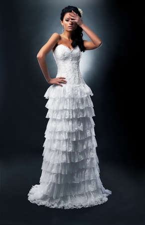 Insulted bride brunette in white dress standing in studio - series of photos photo