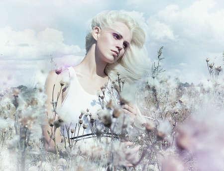 Beautiful gentle blonde girl in flowering meadow