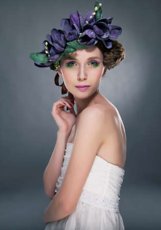 engaging: Luxurious supermodel lovely girl in wreath of flowers looking at camera Stock Photo