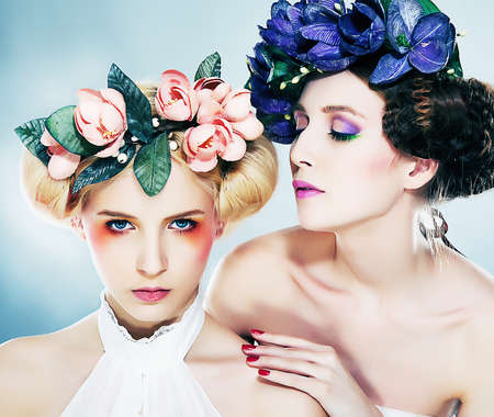 Two sexy nymphs in colorful wreaths touching each other - series of photos Stock Photo - 11927901