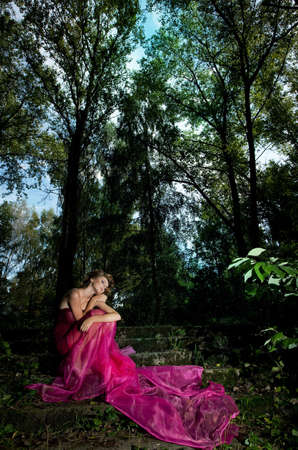 Gentle young girl blonde sitting on stairs in the scenic forest in crimson dress  photo