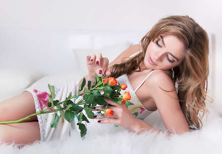 Pretty young girl lying in bed with branch of flower - fresh roses  photo