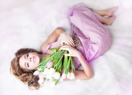 Lovely gentle young woman with bouquet of fresh tulips lying in white bed Stock Photo - 11942106