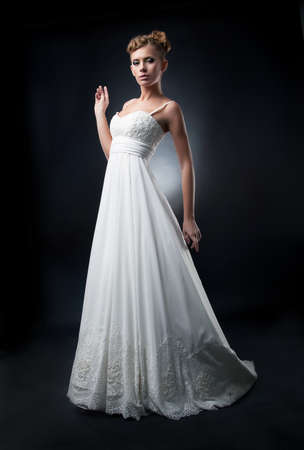Romantic lovely bride fashion model demonstrates white wedding dress photo