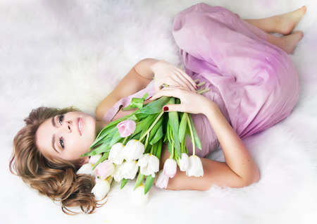 Romantic lovely young girl with bouquet of fresh tulips Stock Photo