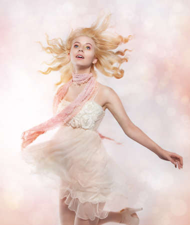 Adolescence - happy lovely young woman blonde in pink clothes photo